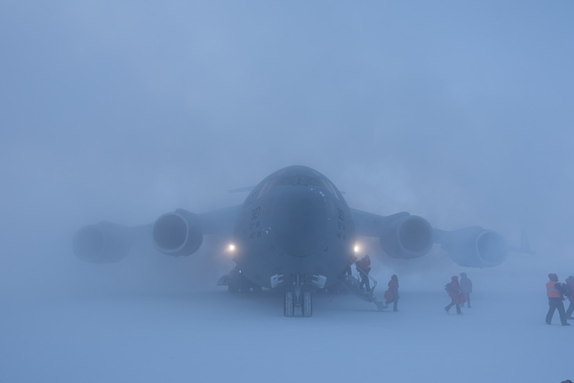 A large aircraft is barely seen through snow mist as people walk to the aircraft.