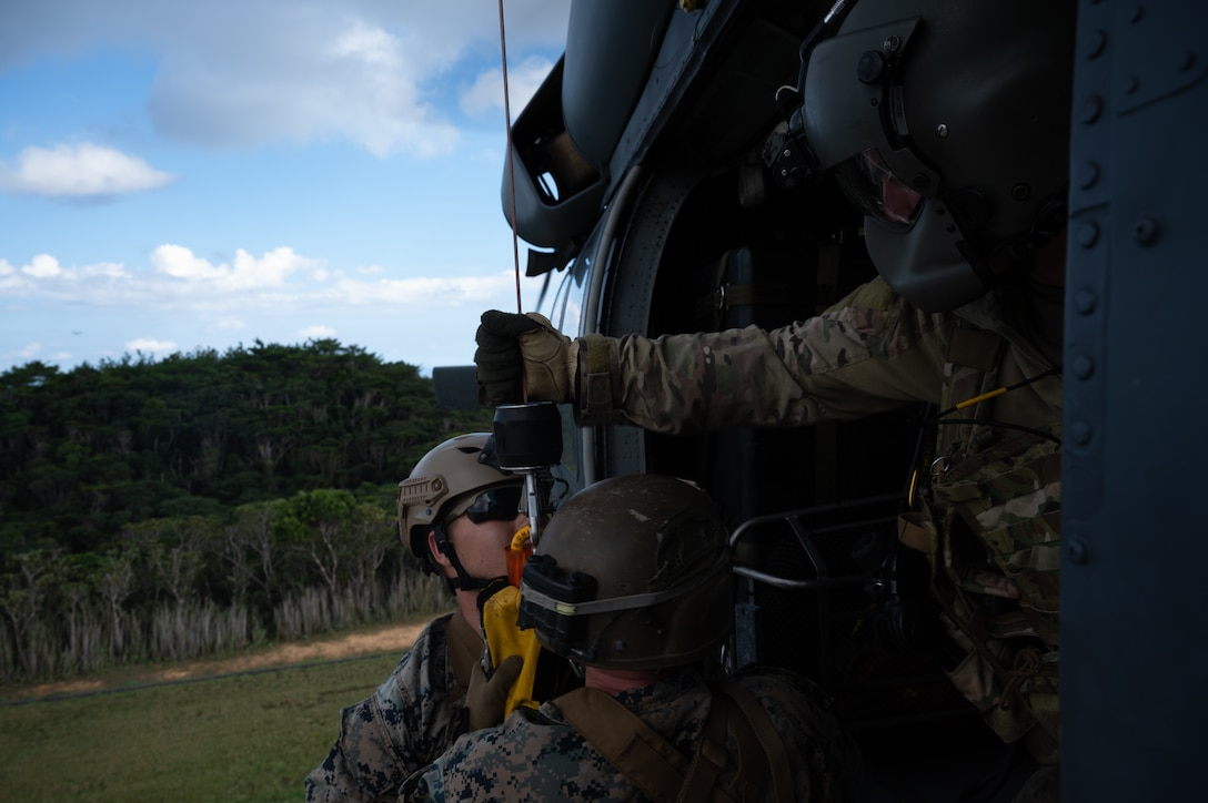 Staff Sgt. Connor Farrell, 33rd Rescue Squadron special missions aviator, helps two U.S. Marines from the 3rd Reconnaissance Battalion enter an HH-60 Pavehawk helicopter at Camp Gonsalves, Japan, Sept. 23, 2021. Joint training ensures there's a shared understanding of strategies, decision-making, method of operations and capabilities. (U.S. Air Force photo by Airman 1st Class Stephen Pulter)