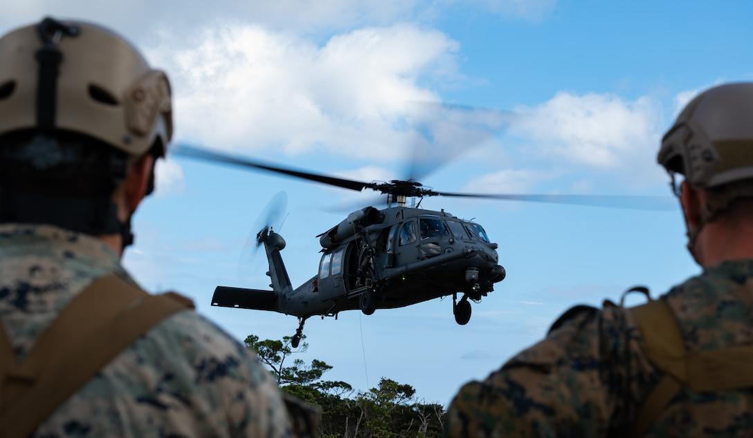 U.S. Marines from the 3rd Reconnaissance Battalion observe A 33rd Rescue Squadron HH-60 Pavehawk helicopter hovering at Camp Gonsalves, Japan, Sept.23, 2021. The 33rd RQS provides combat search and rescue capabilities to aid in exercises and real-world operations in the U.S. Indo-Pacific Command area of responsibility. (U.S. Air Force photo by Airman 1st Class Stephen Pulter)