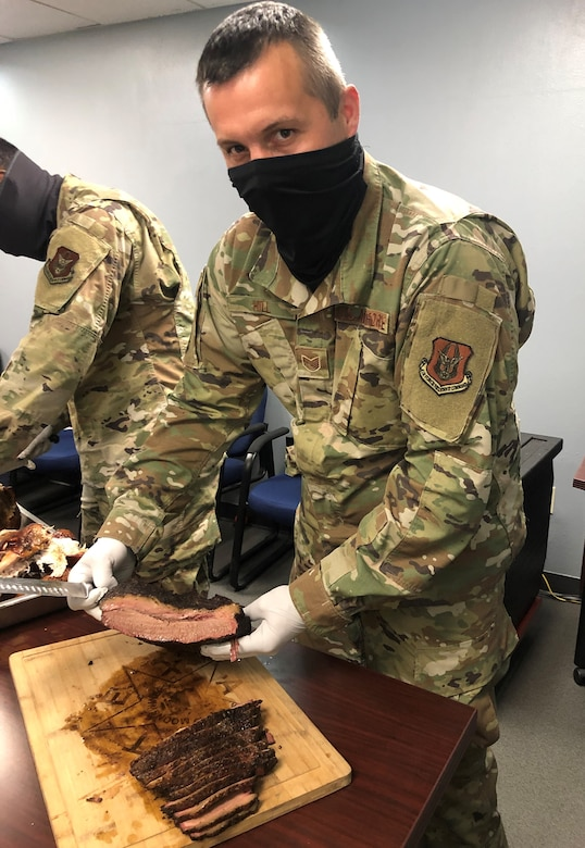 Tech. Sgt. Sean Hill, 73rd Aerial Port Squadron Special Handling Supervisor, serves brisket during the 73d APS 2020 Christmas Lunch event at Naval Air Station Joint Reserve Base Fort Worth, Texas. The pandemic caused Hill to expand his business by vacuum sealing his smoked meats so customers could eat BBQ whenever they wanted, without having to go out as often. Vacuum sealed BBQ will taste like it just came off the smoker up to six months after it is frozen said Hill. (courtesy photo)