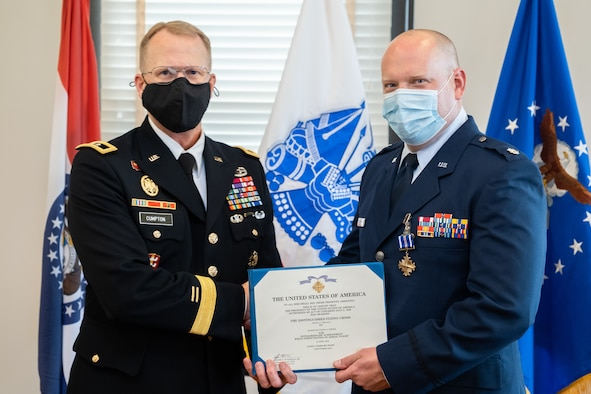 Adjutant General of the Missouri National Guard Maj. Gen. Levon Cumpton presents Lt. Col. Matthew Pieper, a Center for Sustainment of Trauma and Readiness Skills instructor, with the Distinguished Flying Cross during a ceremony at Jefferson Barracks Air National Guard Base, Missouri, September 12, 2021. Pieper was decorated for his lifesaving actions during a 2018 aeromedical evacuation flight while deployed to Afghanistan. (U.S. Air National Guard photo by Master Sgt. Stephen Froeber)