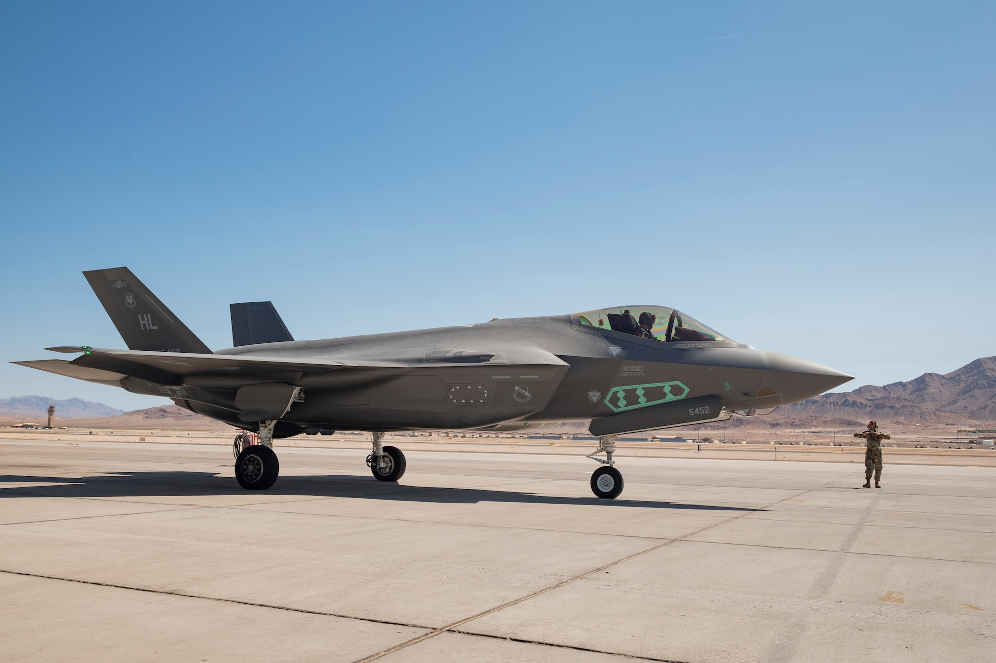 Airman 1st Class Javier Farcia-Bustos marshals an F-35A Lightning II as it taxis to complete the final test exercise of the nuclear design certification process at Nellis Air Force Base, Nevada, Sept. 21, 2021. This event included the first release of the most representative B61-12 test asset from an operationally representative F-35A, resulting in the B61-12 becoming the first F-35 weapon to complete development and intrgration during the aircraft's modernization phase. (U.S. Air Force photo by Airman 1st Class Zachary Rufus)