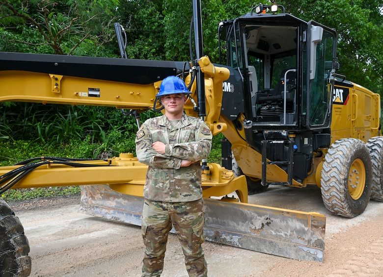 U.S. Air Force Senior Airman Cody Chenowith, pavements and equipment journeyman assigned to the 36th Civil Engineer Squadron, poses for a photo in front of a CAT 12M3 Grader, at Andersen Air Force Base, Guam, Aug. 25, 2021. Pavements and equipment airmen play a vital role in caring for the infrastructure on Andersen AFB. Chenowith spends his days balancing his duties at the 36th CES, base Honor Guard and re-launching the Guam Civil Air Patrol chapter, where he leads his team as the Andersen Flight Commander. (U.S. Air Force photo by Tech. Sgt. Esteban Esquivel)