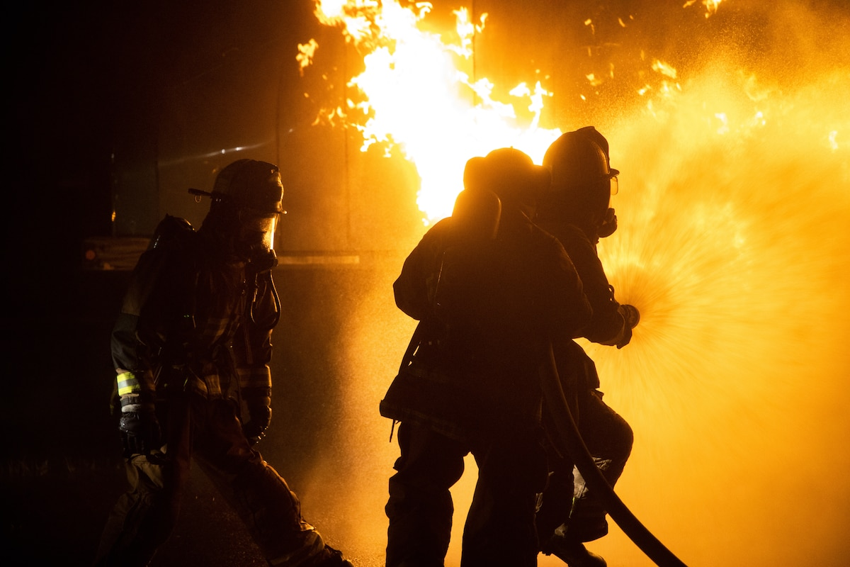 Marines are silhouetted against a blazing fire.