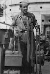 Cesar Romero at the controls of Cavalier's ship's crane. (Coast Guard Collection)
