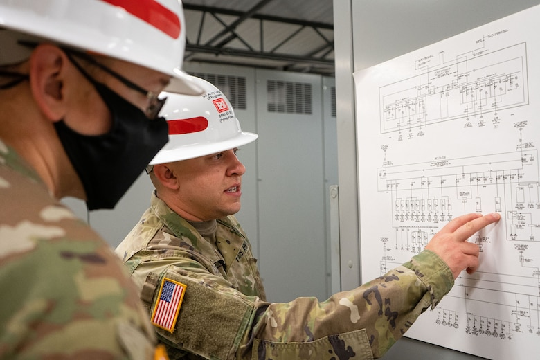 U.S. Army Sgt. Logan Cummings, back, examines an electrical one-line diagram alongside fellow 249th Engineer Battalion Charlie Company Prime Power production specialist Staff Sgt. Daniel Dipilato, during Exercise Empire Rising 2021 at the U.S. Naval Academy in Annapolis, Md., July 13, 2021. The U.S. Army Corps of Engineers, Baltimore District; 249th Engineer Battalion Charlie Company Prime Power; and emergency management partners helped enable community restoration efforts in the National Capital Region by successfully assessing temporary emergency power needs for critical facilities after a mock hurricane. (U.S. Army photo by Greg Nash)