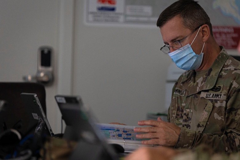 """Chief Warrant Officer 2 Ferencz Babinszki, 249th Engineer Battalion Charlie Company Prime Power mission commander, operates in an emergency operations center during Exercise Empire Rising 2021 in Baltimore, Md., July 15, 2021. Empire Rising is a validation exercise that challenged the 249th EB Charlie Company """"Spartans"""" and U.S. Army Corps of Engineers, Baltimore District, to successfully coordinate hurricane preparedness and response efforts during a mock tropical storm. (U.S. Army photo by Greg Nash)"""
