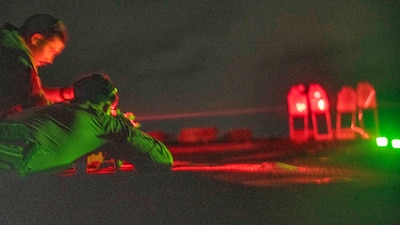A corpsman sights in with an M4A1 carbine during a night-time live-fire range aboard USS Pearl Harbor (LSD 52).