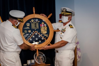 Capt. Keith Dowling, right, receives a shadow box as part of his retirement ceremony held during a change of command for the Center for Explosive Ordnance Disposal and Diving  (CEODD), Sept. 22.  Dowling retired after nearly 38 years of service in the U.S. Navy.