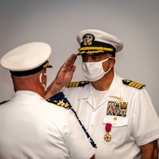 After 38 years of naval service, Capt. Keith Dowling, right, receives a U.S. flag during his retirement ceremony, Sept. 22.  The ceremony was held during a change of command for the Center for Explosive Ordnance Disposal and Diving (CEODD), where Dowling concluded his career as CEODD's commanding officer.