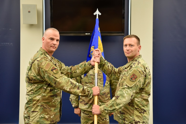 Lt Col. Aaron Gulczynski (right) receives the guidon from Col. Timothy Guy (left) during the 128th Air Refueling Wing Logistics Readiness Squadron change in command ceremony in Milwaukee, Wisconsin, Aug. 8, 2021. The Logistics Readiness Squadron provides unparalleled support to the 128 ARW refueling mission.  (U.S. Air Force photo by Senior Airman Madison Knabe)