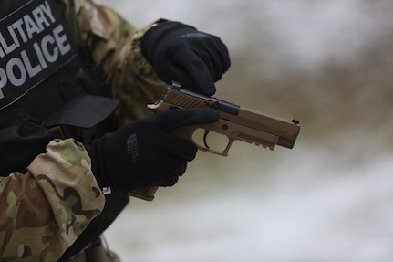 Soldier points out parts of new M17 pistol.
