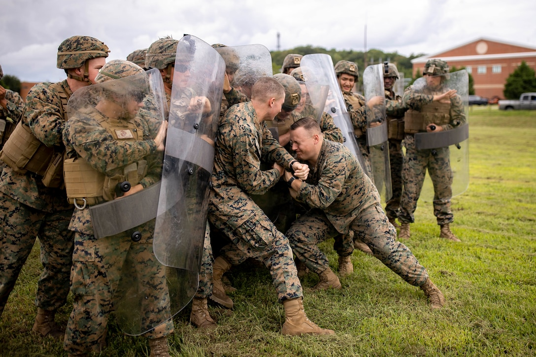 Marines wearing protective gear and holding clear barriers push off fellow Marines during training.