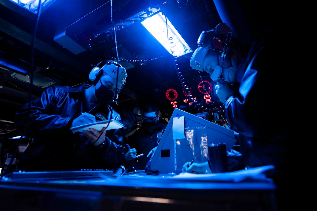 Two sailors illuminated by blue light wear headphones while one writes on a notepad.