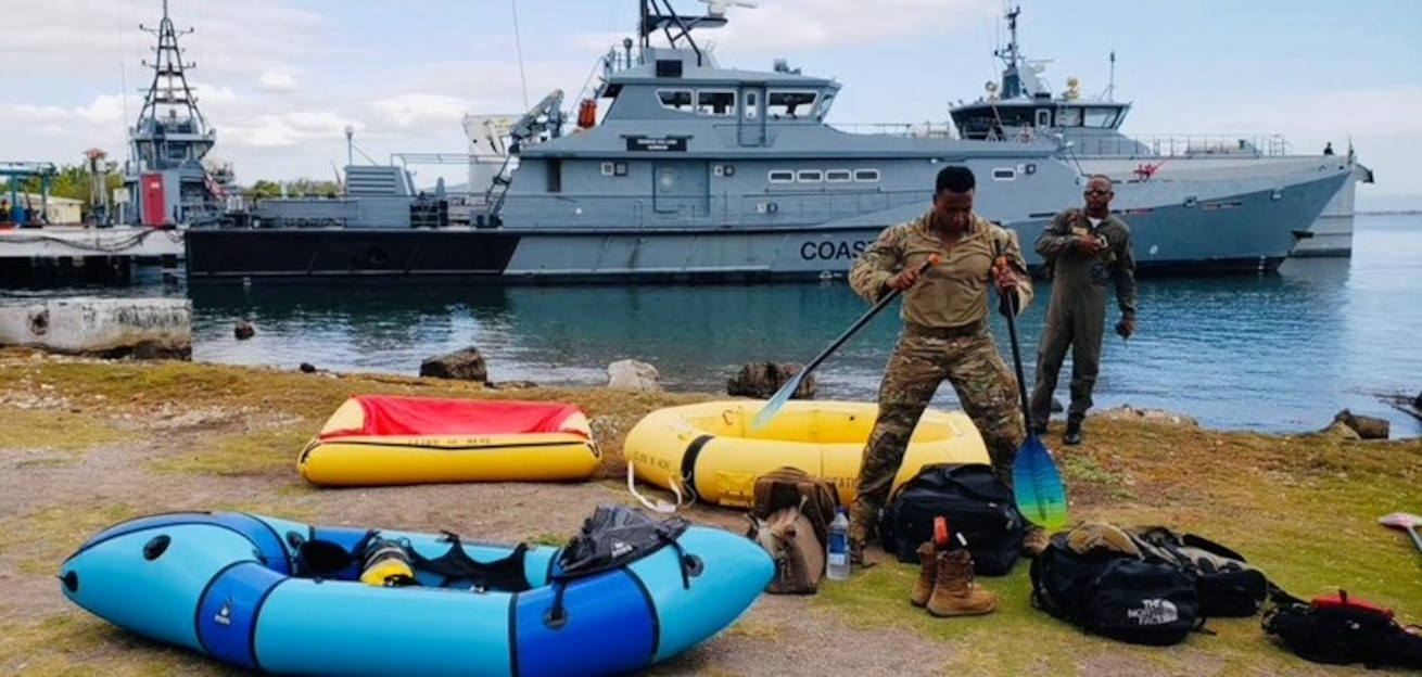 Jamaican service member on shore with survival equipment and ships in background.