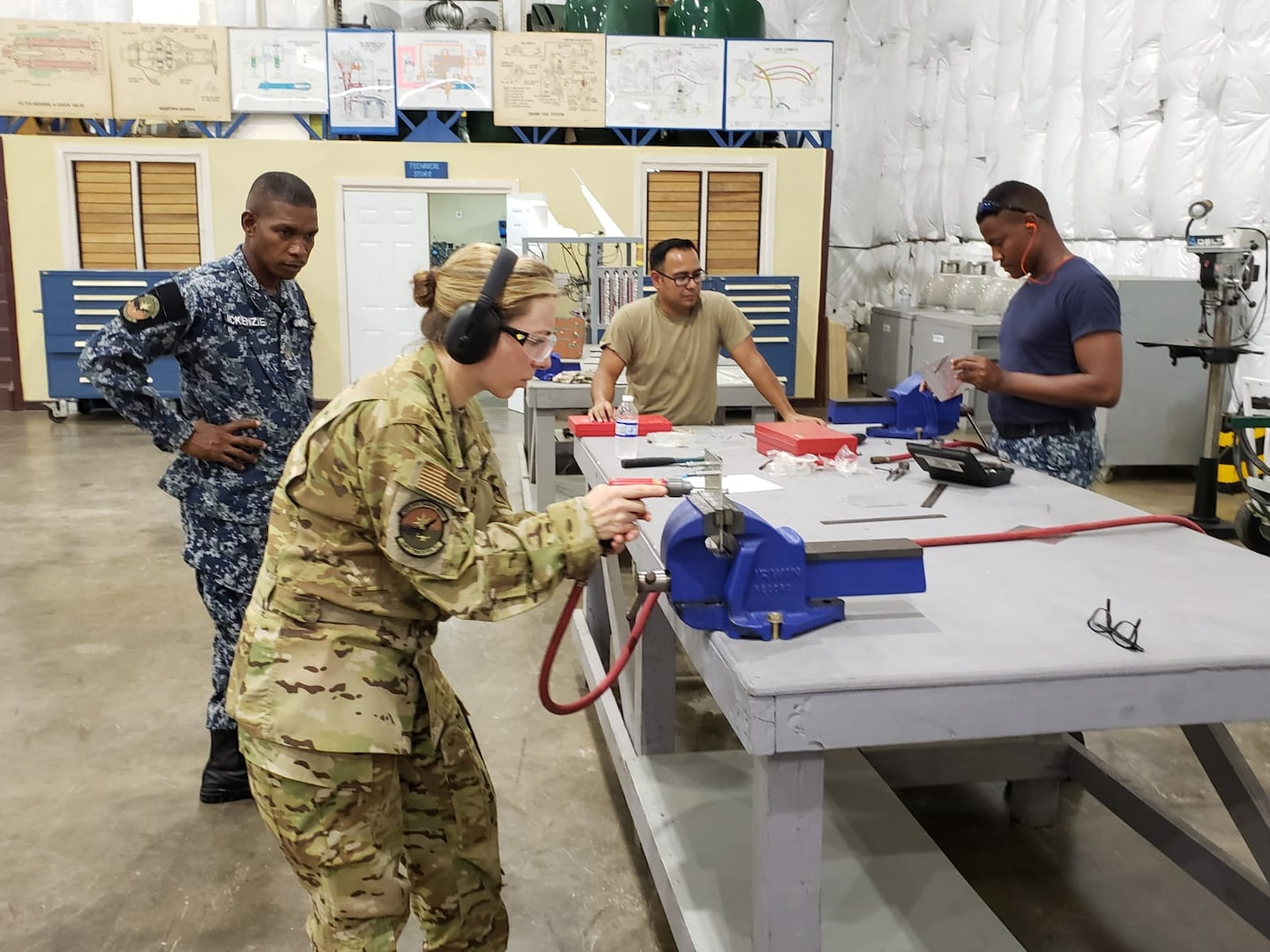 Air Force lieutenant colonel shows how to operate an impact driver to Jamaican service members.