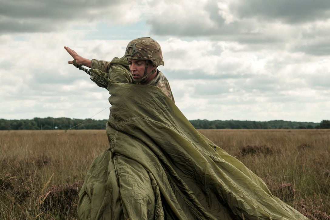 An Army paratrooper gathers a parachute canopy in a field.