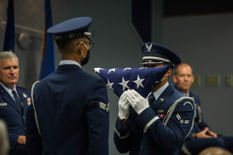 Base Honor Guard airman hands a folded American flag to another Honor Guard member.