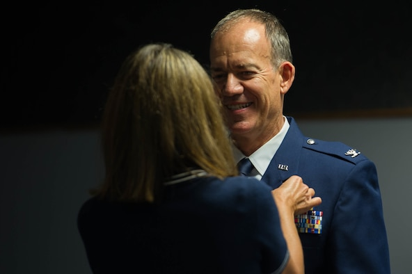 Woman fastens a retirement pin on airman.
