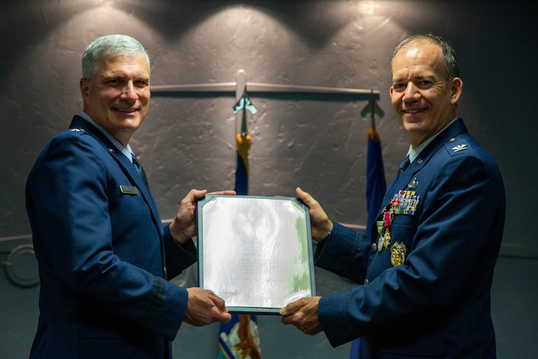 Two airmen hold a certificate.