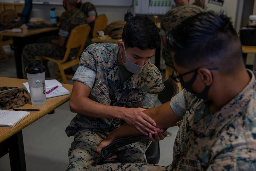 A Marine practices applying a splint on the arm of another Marine.
