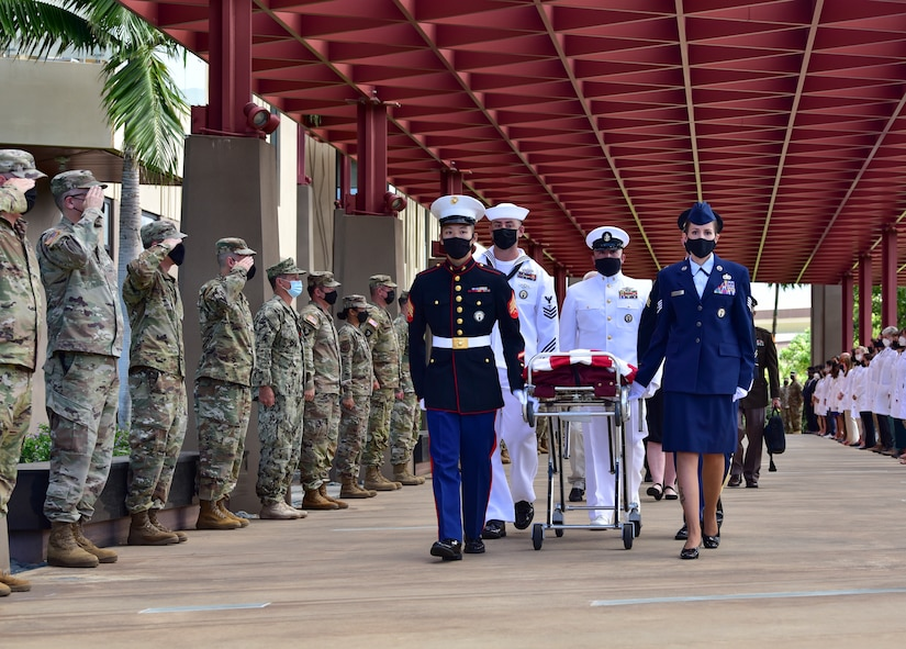 Service members walk with a flag-draped casket as fellow troops salute.