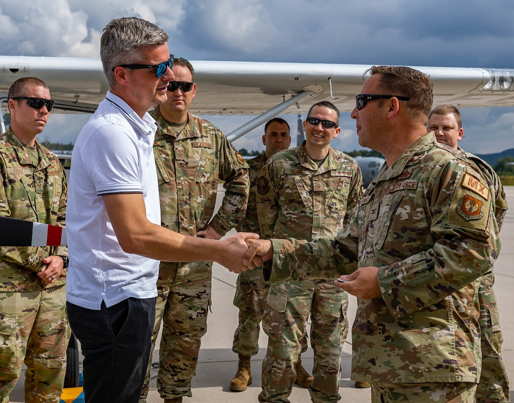 Commander shakes hand with aircraft trainer.