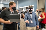 Lifecycle Engineering representative Cory Kozlowski, left, helps Brian Hoglund, a Keyport computer scientist, use a mixed-reality headset Wednesday, Aug. 25, 2021, during Puget Sound Naval Shipyard & Intermediate Maintenance Facility's 2021 Technology Showcase at the Kitsap Conference Center in Bremerton, Washington. (PSNS & IMF photo by Scott Hansen)