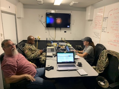 three people sit around a table in a mobile command center