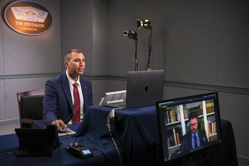 A  man sits in front of several computer monitors at the Pentagon.