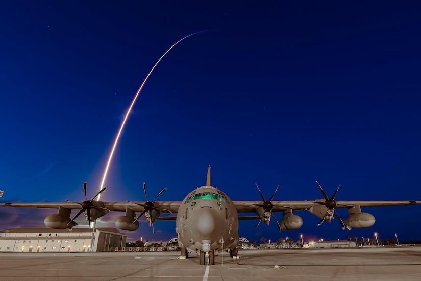 A rocket launches behind an aircraft.