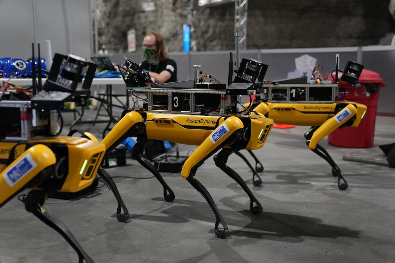 People gather around robots.