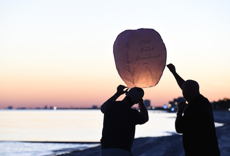 Military family members release a lantern during the Air Force Families Forever Fallen Hero Sky Lantern Lighting on the Biloxi Beach, Mississippi, Sept. 24, 2021. The event, hosted by Keesler Air Force Base, included eco-friendly sky lanterns released in honor of fallen heroes. (U.S. Air Force photo by Kemberly Groue)