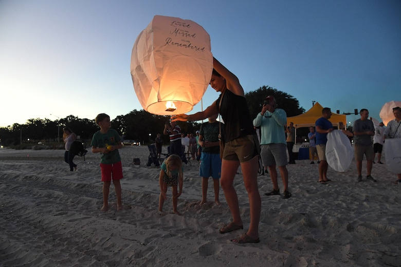 U.S. Air Force Capt. Heather Prentice, 81st Operational Medical Readiness Squadron mental health provider, prepares to release a lantern during the Air Force Families Forever Fallen Hero Sky Lantern Lighting on the Biloxi Beach, Mississippi, Sept. 24, 2021. The event, hosted by Keesler Air Force Base, included eco-friendly sky lanterns released in honor of fallen heroes. (U.S. Air Force photo by Kemberly Groue)
