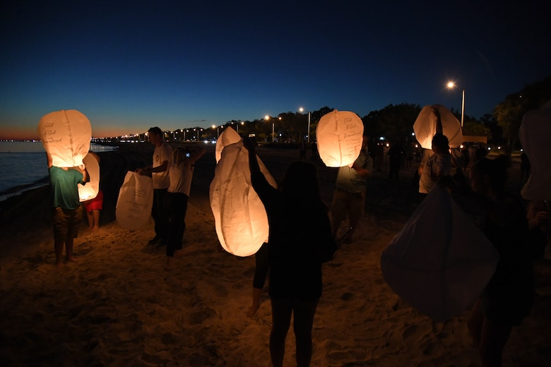 Military family members light lanterns during the Air Force Families Forever Fallen Hero Sky Lantern Lighting on the Biloxi Beach, Mississippi, Sept. 24, 2021. The event, hosted by Keesler Air Force Base, included eco-friendly sky lanterns released in honor of fallen heroes. (U.S. Air Force photo by Kemberly Groue)