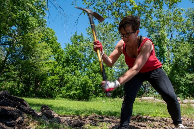 a woman swings a pick axe.