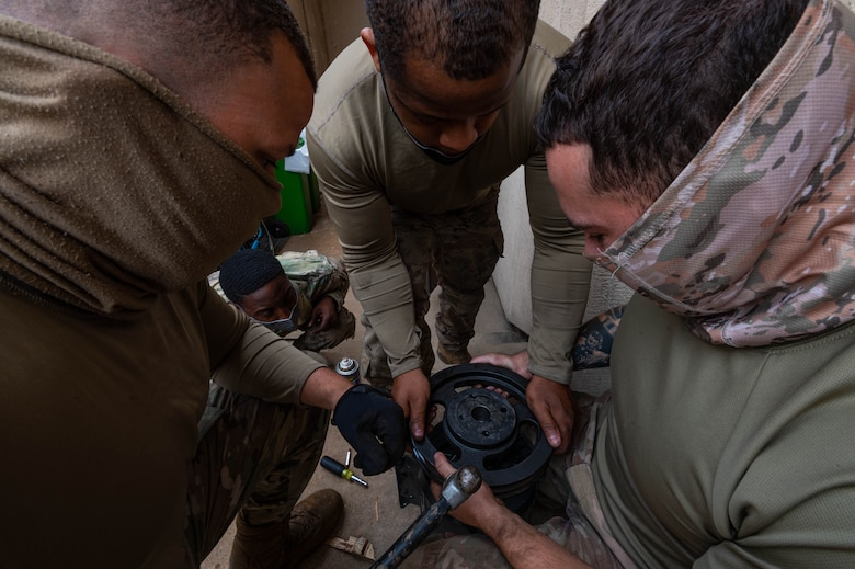 51st Civil Engineering Squadron heating ventilation and air conditioning (HVAC) technicians, take a usable pulley off of a defective motor and attach it to a working air handling unit motor