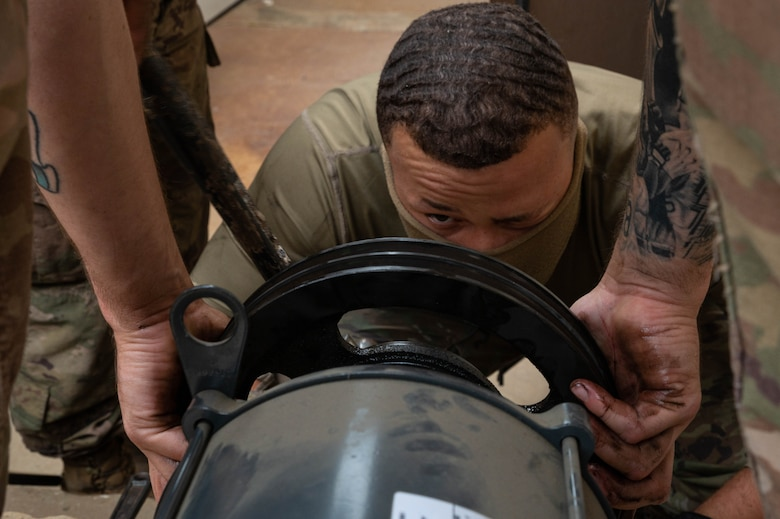 Senior Airman James Stone, 51st Civil Engineering Squadron heating ventilation and air conditioning (HVAC) technician, checks the alignment of a pulley