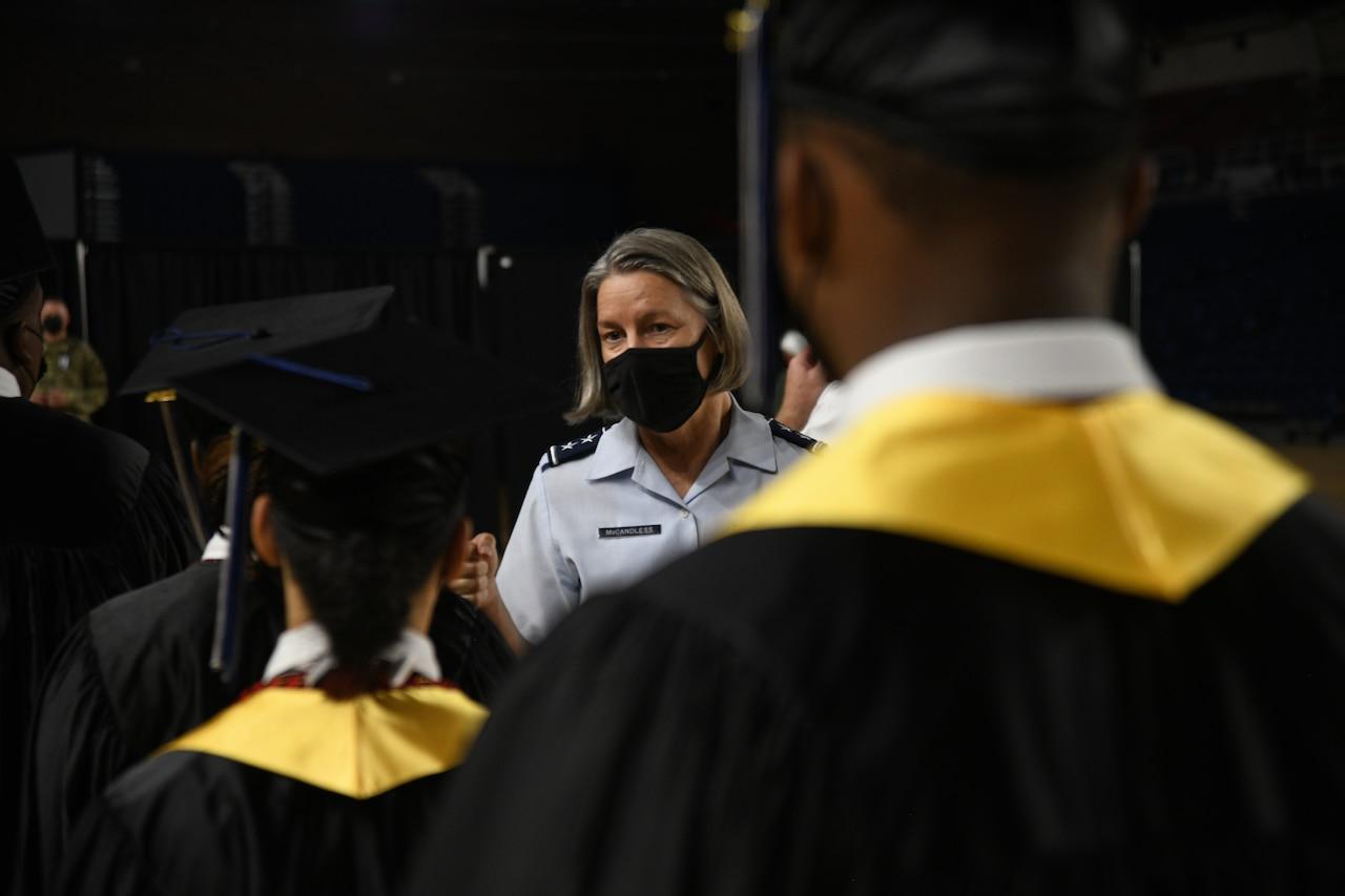 A female airman looks toward three people in graduation garb.