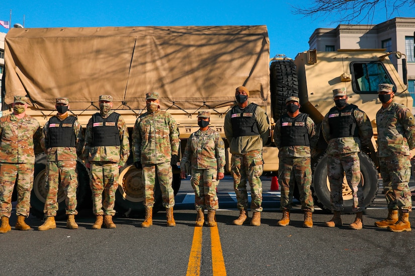 Nine service members in uniform, some of whom wear vests, pose in front of a large military truck.