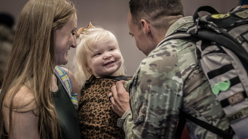 A soldier greets a smiling woman and child.