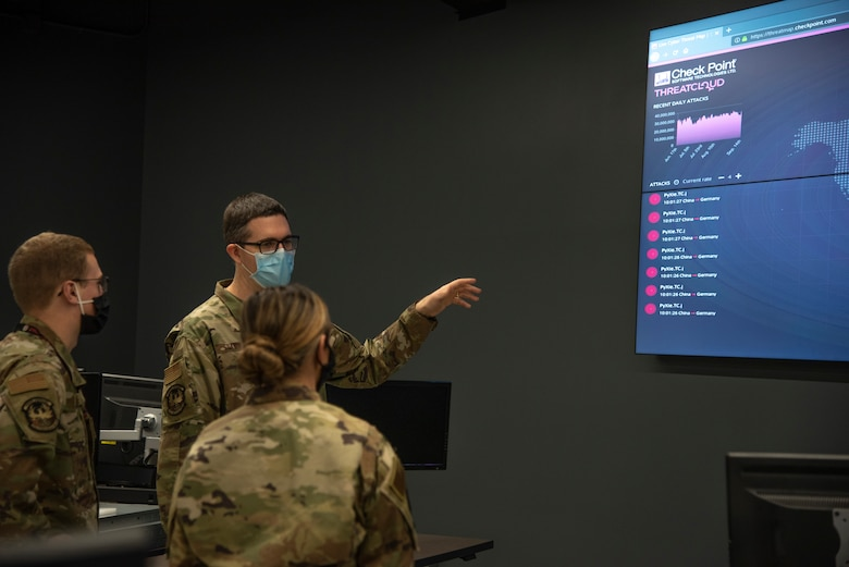Maj. Richard Frantz, 272nd Cyber Operations chief of training, explains the Threat Cloud program to Senior Airmen Kelsie Hubbart and Micah Sage, cyber operators on the operations floor at Battle Creek Air National Guard Base, Michigan, Sept. 14, 2020. Threat Cloud was used to improve traffic conditions for the state of Michigan during Operation Resilience, Innovative Readiness Training.