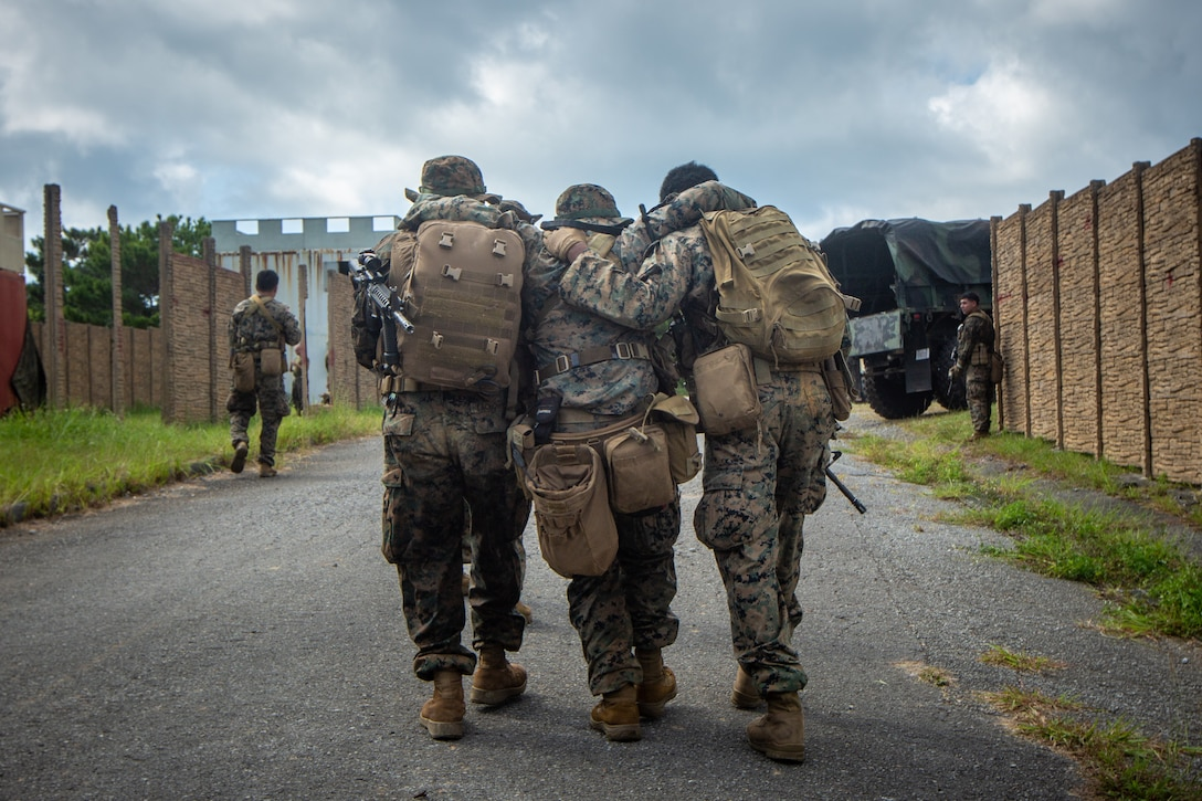 U.S. Marines assigned to 5th Air Naval Gunfire Liason Company, III Marine Expeditionary Force Information Group, simulate a buddy carry during a patrol while conducting a communications planning exercise on Camp Hansen, Okinawa, Japan, Sept. 23, 2021. The Marines practice patrolling to allowthem to  move from position to position tactically and safely under combat conditions. III MIG functions as the vangaurd of III MEF, operating in the Indo-Pacific region's information environment, and supports Marine Air Ground Task Force operations with communications, intelligence, and supporting arms liason capabilities.