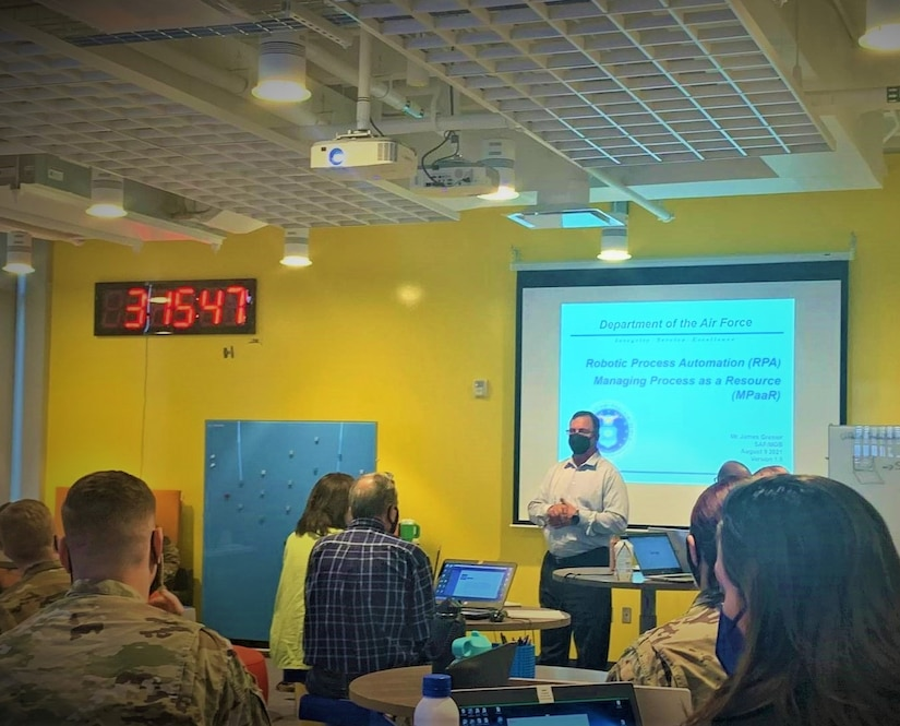 A man presents information at the front of a classroom.