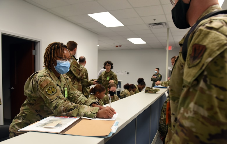 Photo shows Airmen talking with personnel behind counter.