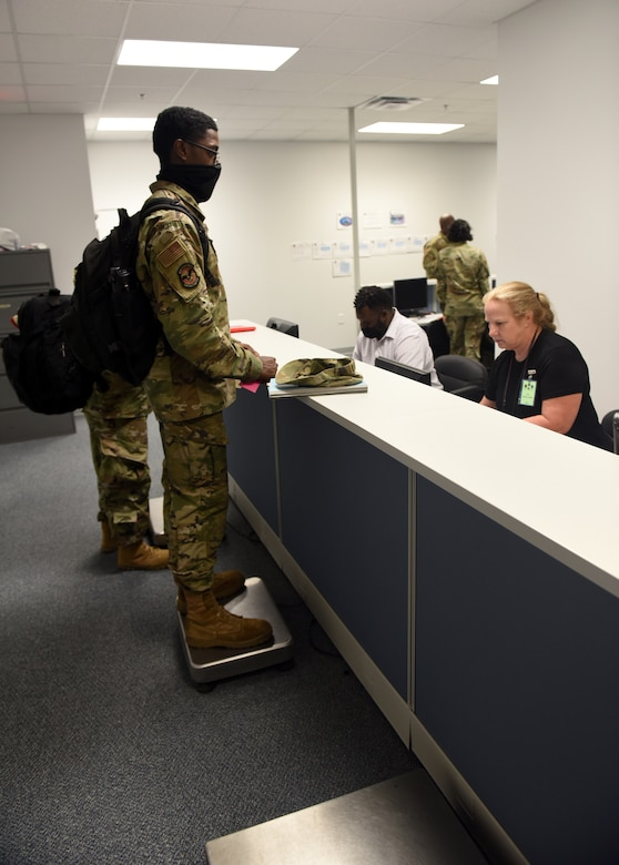 Photo shows Airmen walking by counter with personnel behind camera.