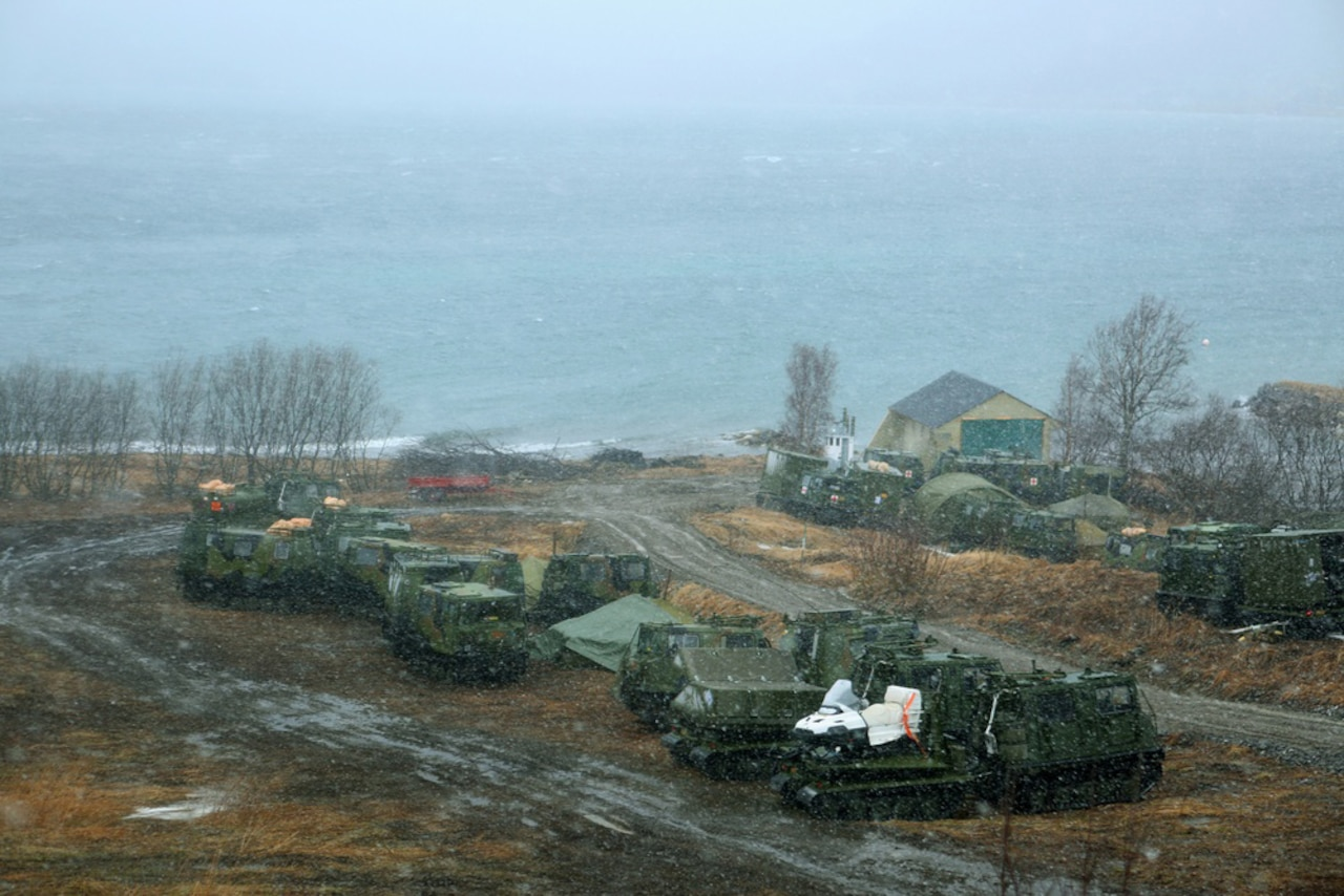 Military vehicles are parked in a muddy area along a coastline.