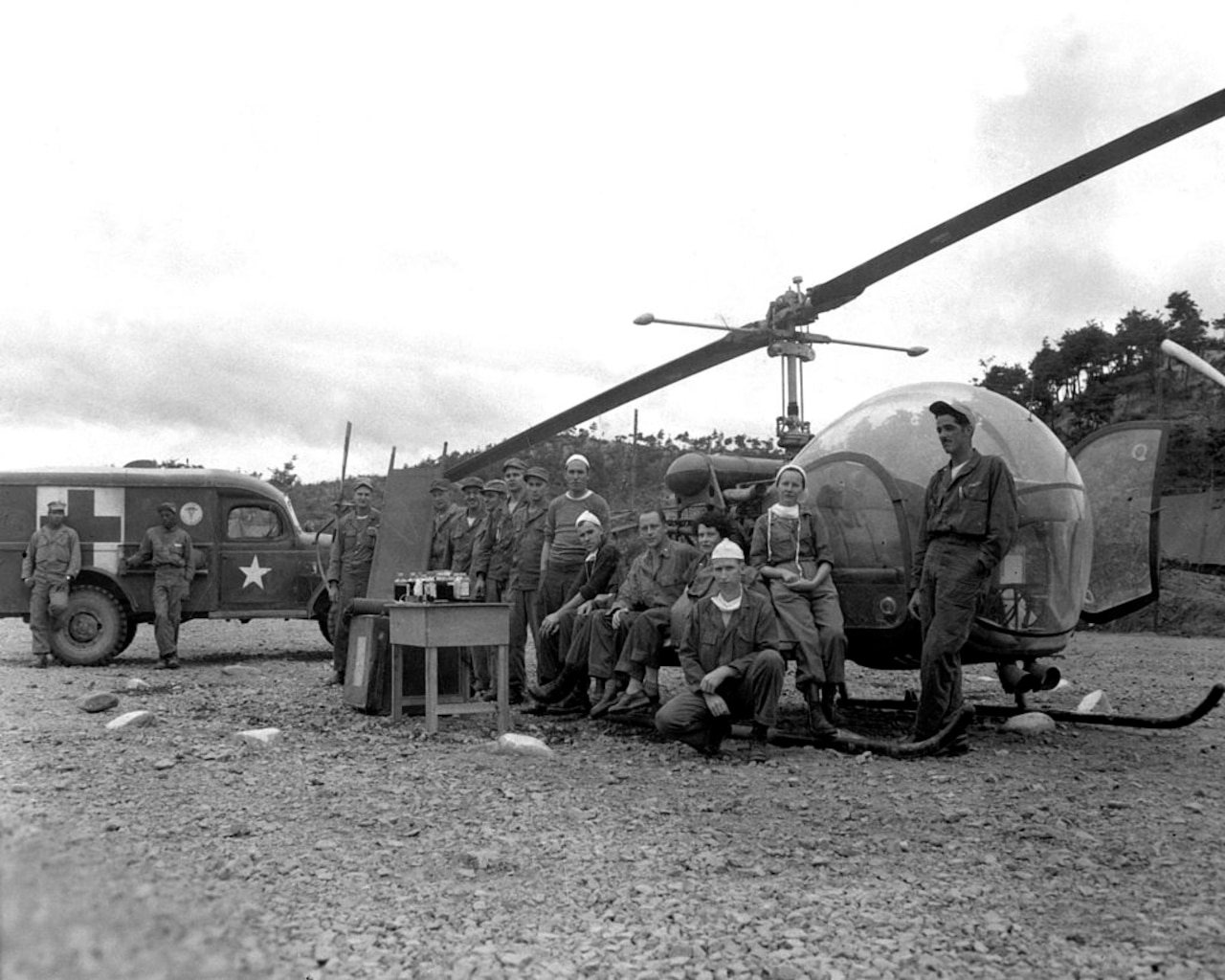 People pose for a photo in front of a helicopter.