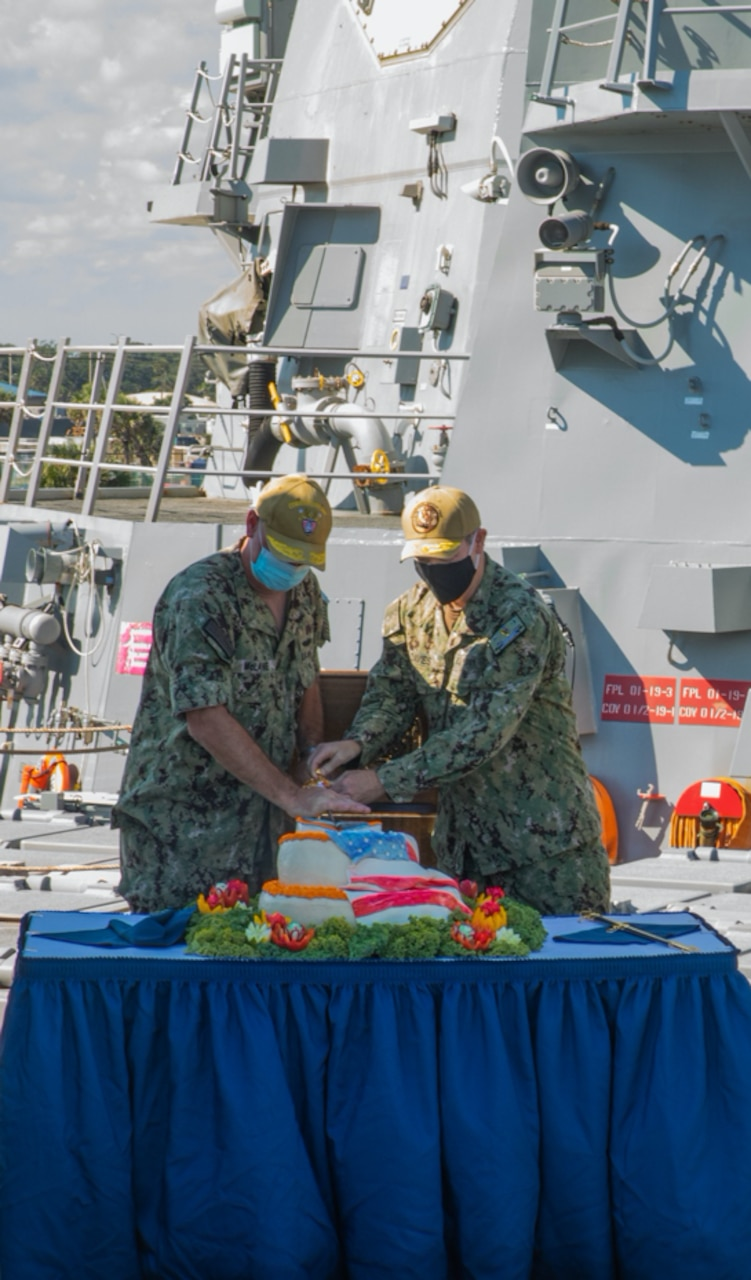 Rear Adm. Brendan McLane, commander, Naval Surface Force Atlantic, left, and Rear Adm. Brian Davies, commander, Submarine Group Two, right, cut a cake following introducing the Task Group Greyhound Initiative (TGG) aboard the guided-missile destroyer USS Thomas Hudner (DDG 116). TGG is a force generation initiative, inside the Optimized Fleet Response Plan (OFRP) construct, designed to provide the Fleet with predictable, continuously ready, and fully certified warships ready to accomplish the full range of fleet tasking. (U.S. Navy photo by Mass Communication Specialist 3rd Class Aaron Lau/Released)