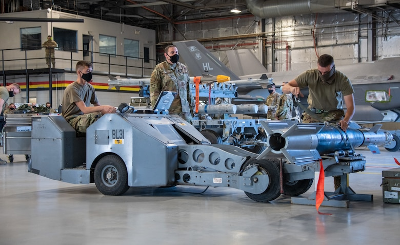 A judge watches two Airmen from the 419th Aircraft Maintenance Squadron load and secure an unarmed GBU-12 Pave Way to a bomb lift during a weapons load competition at Hill Air Force Base, Utah on Sept. 24, 2021. The quarterly competition focuses on speed, accuracy, and safety, ensuring standard loading procedures and proficiency across the wings. (U.S. Air Force photo by Senior Airman Erica Webster)